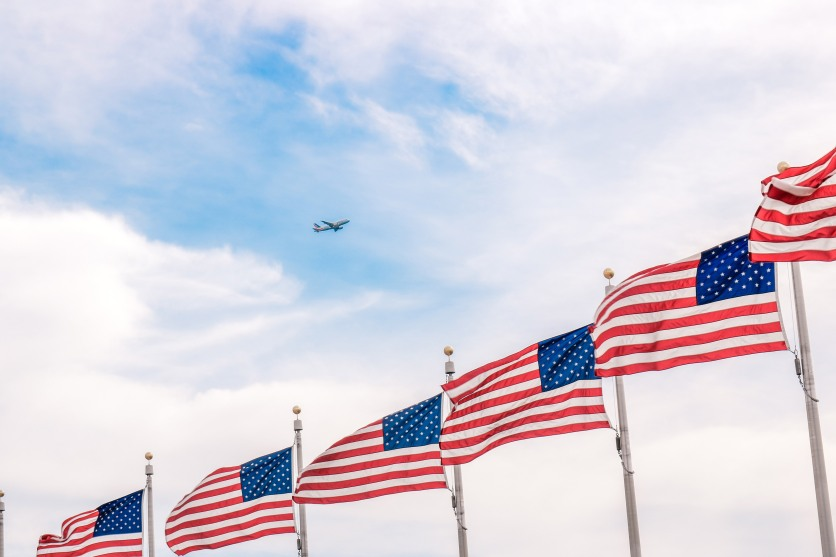 plane-flying-above-a-bunch-of-usa-flags